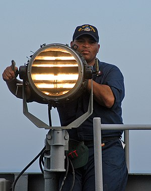 Signal lamp - US Navy sailor sending Morse code using a signal lamp.