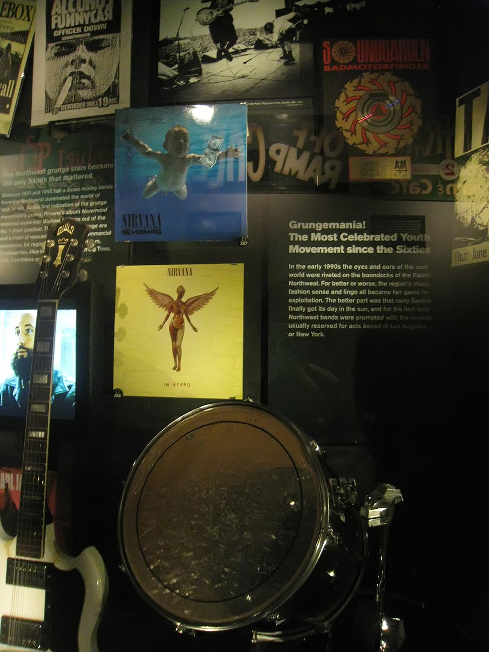 A museum exhibition of items associated with the 1990s Seattle music scene, including two Nirvana record album sleeves, a Soundgarden record sleeve, and instruments.