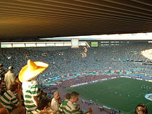 A top-stand perspective of one end of a stadium packed with people wearing white and green shirts as a football match takes place in the pitch. In the foreground, one of these people is wearing a Mexican hat.
