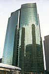 Ground-level view of a high-rise's green, curved, reflective glass facade; it is bisected by a vertical groove