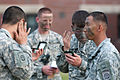 Spc. Cody Olivier applies camouflage paint to his face prior to an airborne training operation.jpg