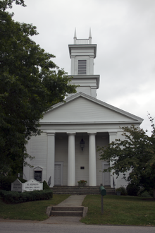 A white church with four narrow points atop its square steeple and columns in front of its entrance flanked by tall trees.