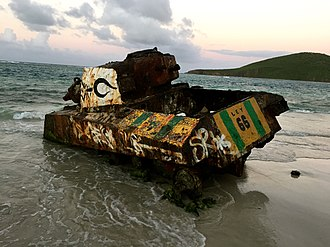 Flamenco Beach - A rusty Sherman tank half-buried on Flamenco Beach.