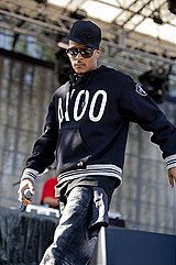 T.I. walking onto a stage wearing a cap, hoodie, jeans and sunglasses