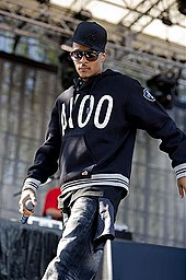 T.I. wearing a black cap and black outfits