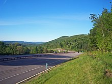 A divided highway curving across the bottom of the picture, passing a hill on the right in the foreground on its way to a more level landscape at left center