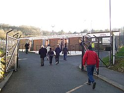 Various people walking towards the entrance to a brick-built sports stadium