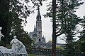 The Basilica of Our Lady of the Rosary of Lourdes, as viewed between trees.jpg