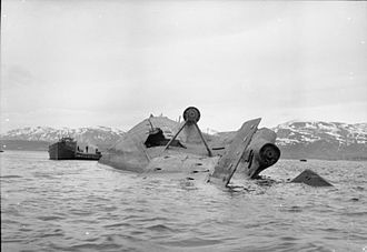 Capsizing - German battleship Tirpitz lying capsized in Tromso fjord after RAF bombing attacks, attended by a salvage vessel.
