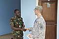 U.S. Army Capt. Lucas Klettke, right, with the 141st Maneuver Enhancement Brigade, North Dakota Army National Guard, shakes hands with a Ghana Army officer June 18, 2013, at the Kofi Annan International 130618-Z-ZZ999-001.jpg