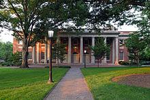 Um grande edifício de tijolo com colunas na frente e três portas.
