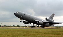 Grande avião a jato cinza com três motores (dois sob as asas e um sob o estabilizador vertical).  A aeronave havia acabado de decolar, com o trem de pouso totalmente estendido.