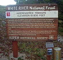 "A brown wooden plaque with ""White River National Forest"" inscribed across the top and explanatory text about the Independence Townsite below"