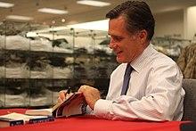 Casual foto van Mitt Romney die binnen zit en boeken signeert