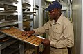 US Navy 031023-N-8295E-036 Chief Warrant Officer (CWO5) Leon A. Cole from Antigua, West Indies, checks recently baked cookies during one of his daily walk through inspections.jpg