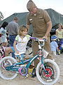 US Navy 041021-N-4204E-048 Chief Electronics Technician Shane Drinkwater helps a child on to her new bike at Ivan Park in Pensacola, Fla.jpg