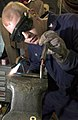 US Navy 060902-N-9851B-007 Hull Technician 2nd Class Benjamin Howe bends the heated end of a metal rod to be used in making a replacement spoke in the steering wheel of a Rigid Hull Inflatable Boat (RHIB).jpg
