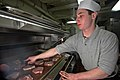 US Navy 070104-N-7883G-006 Culinary Specialist Seaman Rob Exler from Columbia, Md., grills pork chops in the aft galley aboard USS Kitty Hawk (CV 63).jpg
