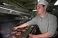US Navy 070104-N-7883G-006 Culinary Specialist Seaman Rob Exler from Columbia, Md., grills pork chops in the aft galley aboard USS Kitty Hawk (CV 63).jpg