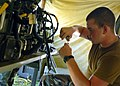 US Navy 070620-N-3857R-001 Personnel Specialist 3rd Class Ray Guedry, of Naval Mobile Construction Battalion (NMCB) 1, splices a communications wire in the ant farm of the battalion's forward operating base (FOB) during Operati.jpg