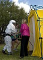 US Navy 071113-N-0184L-022 Naval Hospital Corpus Christi (NHCC) Emergency Response Team member, Hospitalman Walter Mackel, left, assists a victim to the scrubbing area of the decontamination tent.jpg