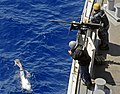 US Navy 090529-N-5345W-090 Sailors standing the forward 50-caliber machine gun station watch as a bottlenose dolphin leaps.jpg