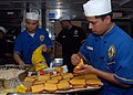 US Navy 100107-N-8607R-052 Culinary Specialist Seaman Dequan Luo and Culinary Specialist 3rd Class Ricardo Carreon prepare tuna melt sandwiches in the main galley aboard USS Bonhomme Richard (LHD 6).jpg
