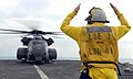 US Navy 111130-N-GH121-426 Boatswain's Mate 2nd Class Brady Laxton signals to a MH-53E helicopter from Helicopter Mine Countermeasures Squadron 15.jpg