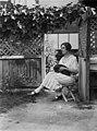 Unidentified women sitting on stool in garden with black cat, 1930s, Sam Hood (29201193474).jpg