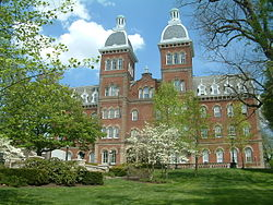 A red brick building with a mansard roof and two identical towers at the top surrounded by trees