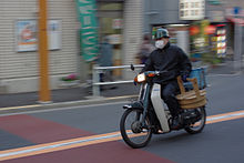 delivery driver riding a yamaha v step through one handed