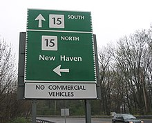 """A sign stating Route 15 south to New Haven to the left. It also states Route 15 north is straight ahead. It says """"No Commercial Vehicles"""""""