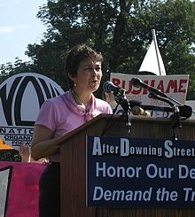 O'Neill speaking at a lectern outside in 2005 amongst lots of signs, NOW logo visible behind her