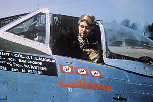 """Lignerolles Airfield - Colonel J.L. Laughlin, of the 362nd Fighter Group, smokes a cigar with his dog mascot """"Prince"""" inside the cockpit of his P-47D serial 44-33287 """"Five By Five"""" (coded B8-A)"""