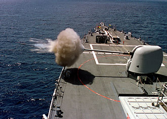 A 5-inch (127 mm)/54 calibre Mark 45 gun being fired from Arleigh Burke-class destroyer USS Benfold 5-54-Mark-45-firing edit.jpg