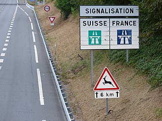 Comparison of European road signs - French sign showing the difference with Swiss signs, on A411 autoroute near Geneva.