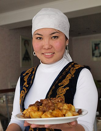 Kyrgyz cuisine - A Kyrgyz woman in national dress delivering a Kyrgyz dish in Bishkek.