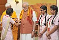 A group of girl students from the Vatsalya Gram Vrindavan tying Rakhi on the Prime Minister, Shri Narendra Modi's wrist, in New Delhi on August 31, 2015.jpg
