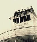 A group of yourng men sitting on top of the cabin of the S.S. Athabasca River.jpg