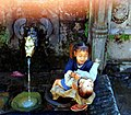 A little Nepalese girl plays with her baby brother near a public fountain, a brass faucet from which water pours, set in concrete and stone, Swayambhunath Temple complex, Kathmandu, Nepal, 1990 (9074647704).jpg