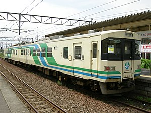 Cream and green-colored Abukuma Express train at Tsukinoki Station