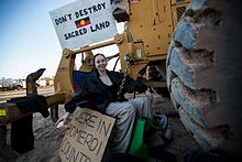 A woman sits with a chain around her waist, padlocked to heavy earthmoving equipment.