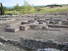 Vestiges de différentes constructions au sol avec des pieds de colonnes et des fondations de forme rectangulaire ou en demi-cercle.