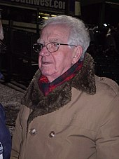 An elderly white man with grey hair and glasses wearing a warm coat and scarf, pictured outdoors at night.