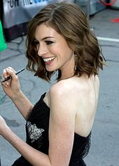 A picture of Anne Hathaway smiling to her right and holding a pen in her right hand.