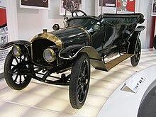 Une voiture ancienne dans un musée, toit découvert, haute calandre, grands phares ronds.
