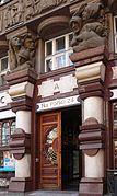 Vue de la porte principale d'un bâtiment, entouré par deux piliers bicolores, ton rouge et blanc, de forme légèrement cylindrique et couronnée par une frise et des statues d'hommes.