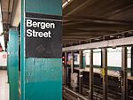 A sign for Bergen Street station with the platforms in the background in 2016