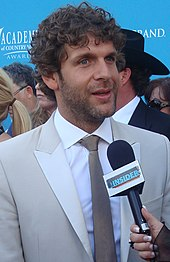 A man with dark curly hair and noticeable beard stubble, wearing a light grey jacket and dark grey tie, talking into a microphone