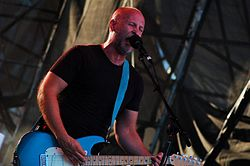 Bob Mould--a middle-aged Caucasian man with a shaved head and short facial hair wearing a black t-shirt--plays a blue guitar and sings into a microphone